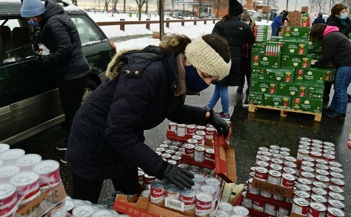 Local residents receive food distributed by volunteers with the CT Food Bank includig Koula Von Hoppe Wednesday, January 27, 2021, in Norwalk, Conn. Distribution events are held Wednesdays at Calf Pasture Beach from 9am to noon.