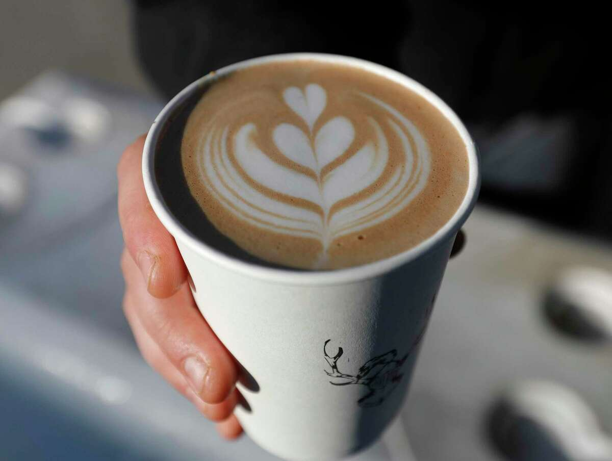 Bradley Bailey, owner of Galavants Coffee, shows a milk design in a latte for a customer at the corner of Metcalf Street and North Main Street, Wednesday, Jan. 13, 2021, in Conroe