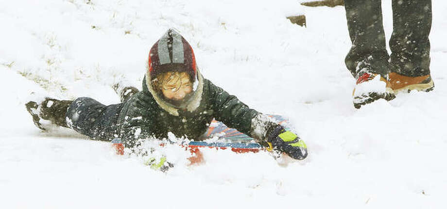 In the 200 block of N. Buchanan St. in Edwardsville, 3-year-old Hugo Sage seemed to be having a blast as he slid down a small hill in the front yard. His brother, Hudson, was doing the same as their father, Adam Sage, supervised.