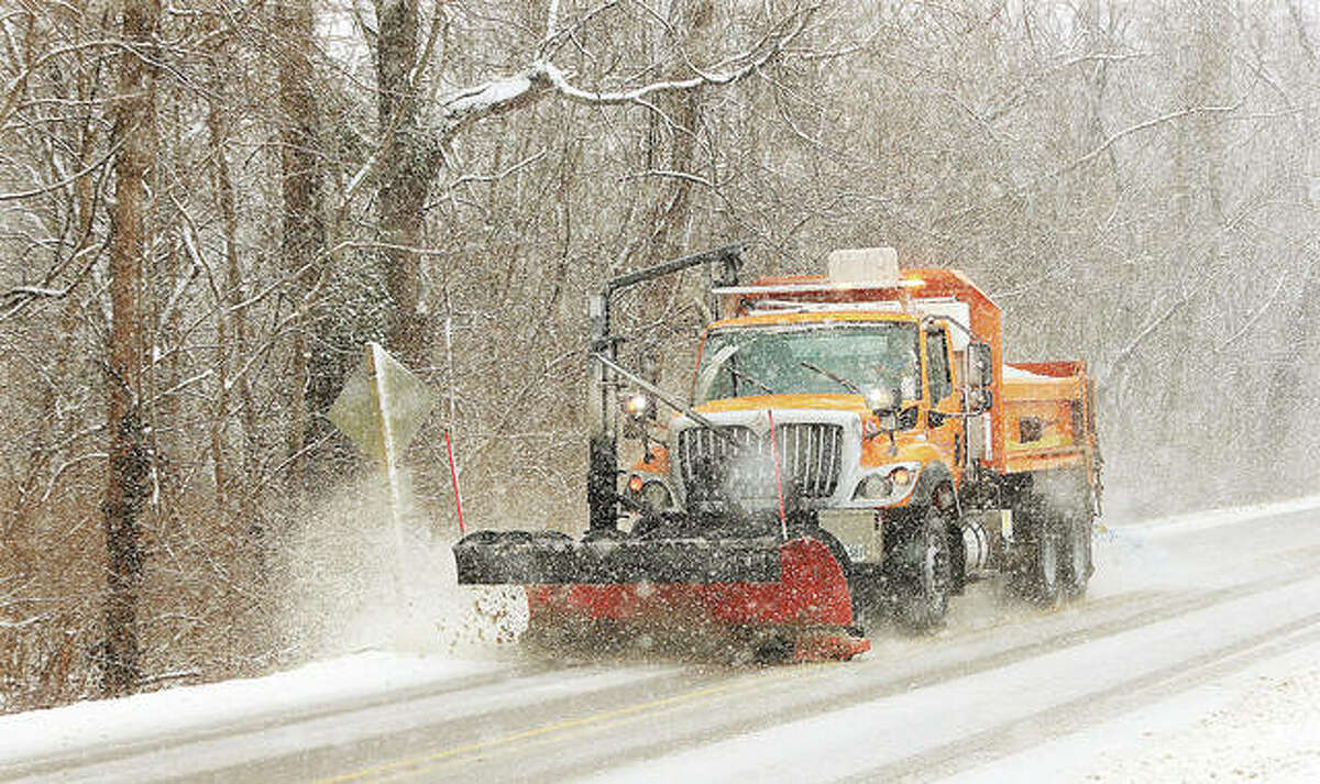 An Illinois Department of Transportation snowplow works to keep up with Wednesday's snowfall on Marine Road in Edwardsville.