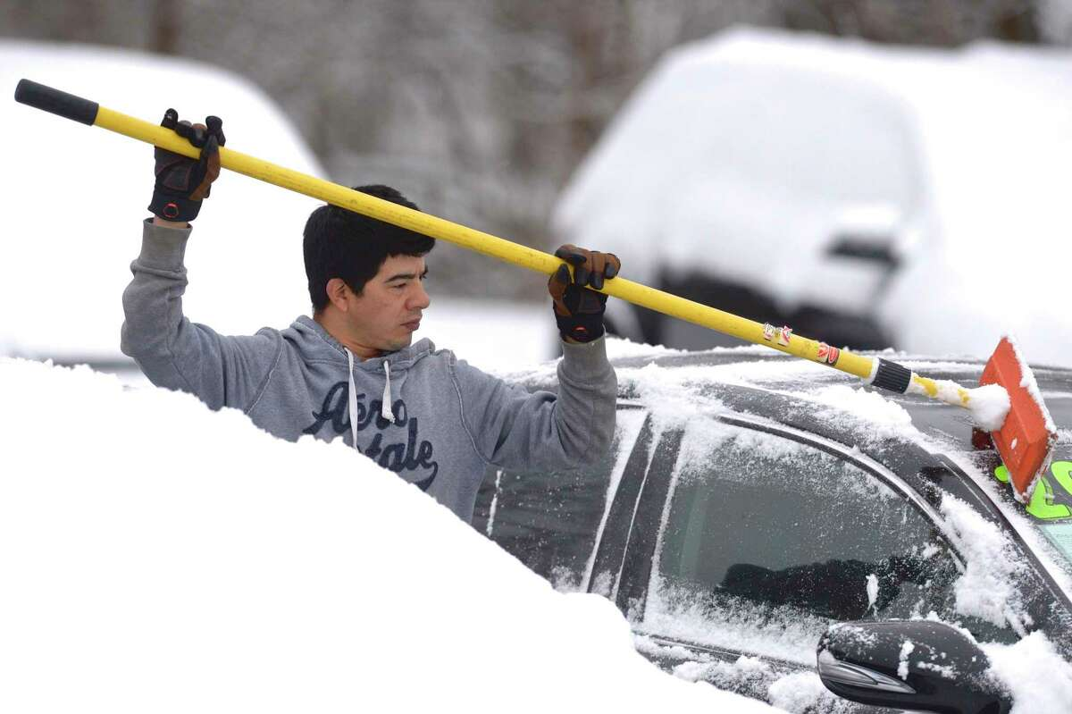 Angel Rodriguez, of Danbury, cleans the snow off of one of over two dozen cars and trucks on the Alves Auto Sales lot on Wednesday morning, January 27, 2021, in New Milford, Conn.