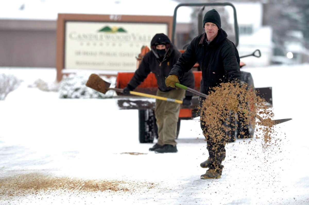 Shawn Andreasen, right, and Mark Pisciotta, from Candlewood Valley public golf course, spread sand across a parking lot on Wednesday morning, January 27, 2021, in New Milford, Conn. Andreasen is the assistant superintendent of the course and Pisciotta is the head mechanic.