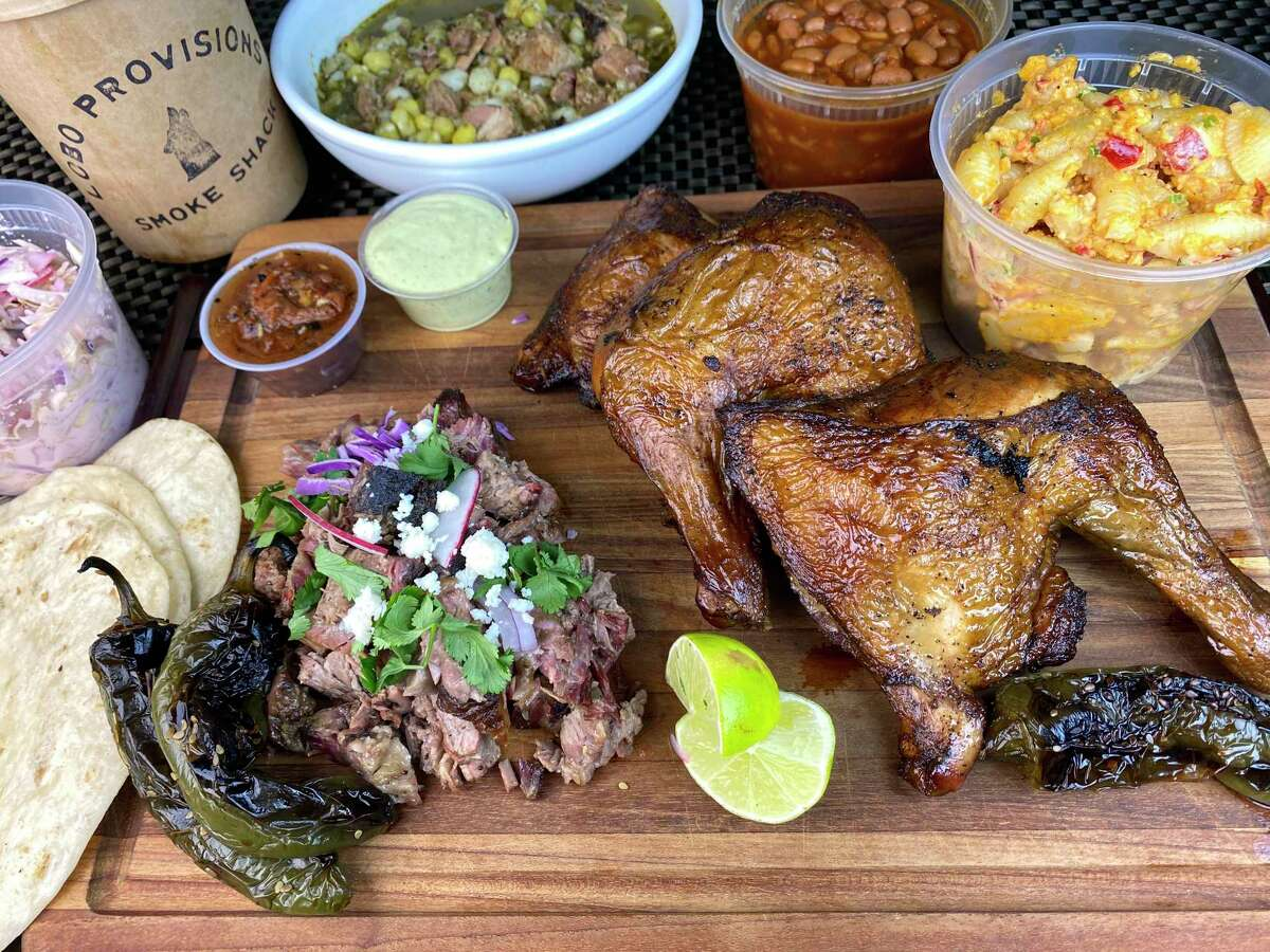 Food from Lobo Provisions Smoke Shack includes, clockwise from bottom left, brisket barbacoa, chiles toreados, coleslaw, smoked pork pozole, barbecue beans, pimento cheese macaroni salad and sweet tea-brined smoked chicken leg quarters.