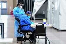 Medical personnel sort through information at the Freeman Coliseum complex on Friday, Jan. 15, 2021, where COVID-19 patients were being given infusions of antibodies.