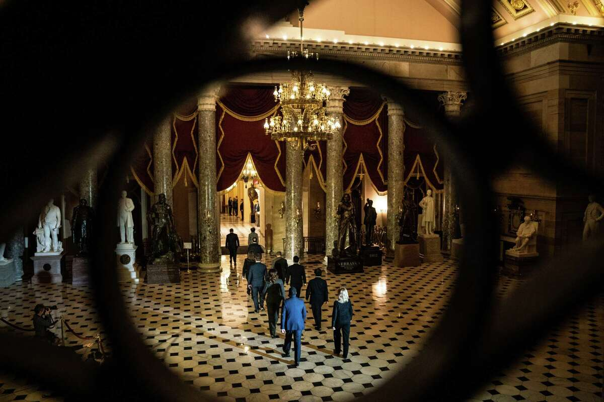 House impeachment mangers walk through National Statuary Hall after leading a procession with the an article of impeachment against former president Donald Trump on Monday, Jan. 25, 2021.