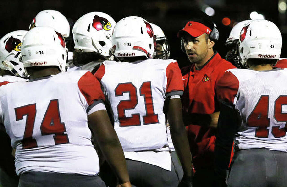 Alton football coach Eric Dickerson (middle right) huddles with his team during a timeout in a SWC victory at O'Fallon on Oct. 4, 2019. The Redbirds' 2020 season will come in 2021, starting with opening night on March 19.