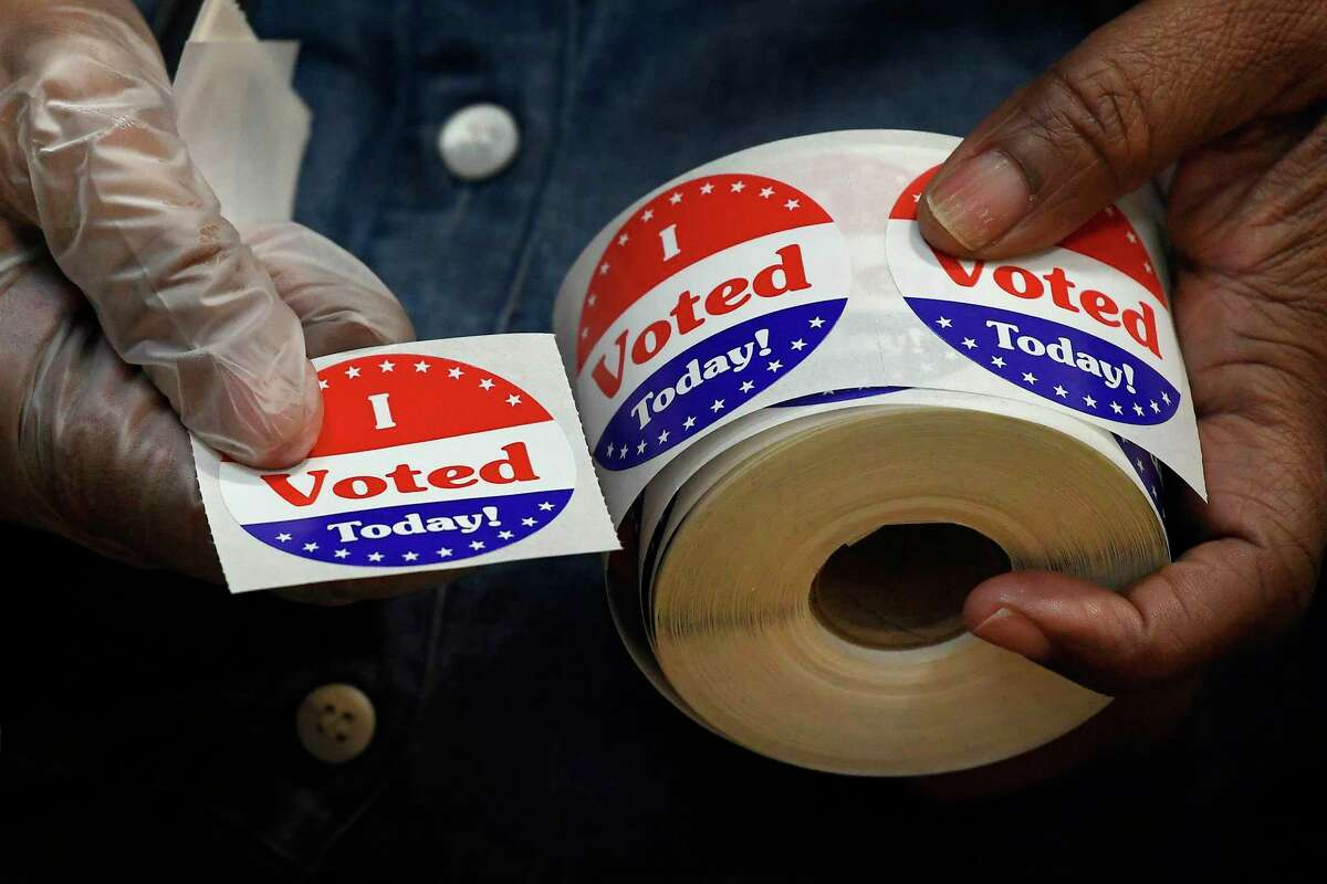 A volunteer holds a sticker to give to a voter at a polling place on Election Day, Nov. 3, 2020, in Stamford.
