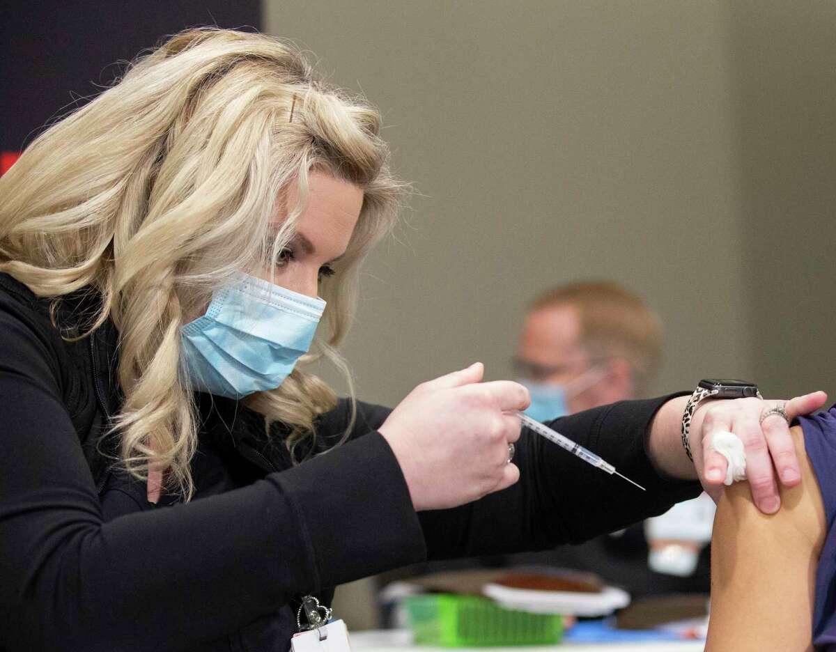 UTMB Galveston Registered Nurse Michelle Garza performs a shot of the Pfizer Covid-19 vaccine Tuesday, Dec. 15, 2020, in Galveston.