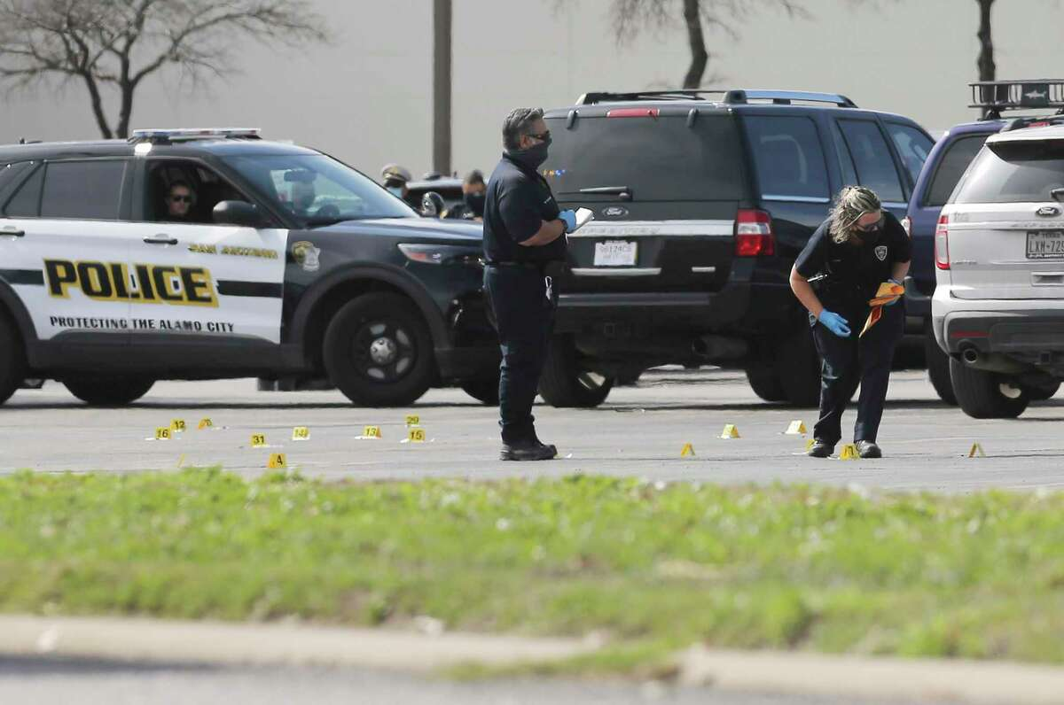 San Antonio police officers gather evidence in a parking lot at South Park Mall where four officers killed a man on Wednesday, Jan. 27, 2021. Police Chief William McManus said the man had a gun when he entered the mall while trying to elude a state enforcement officer who had pulled him over. The man had been driving a tractor-trailer on Interstate 35.