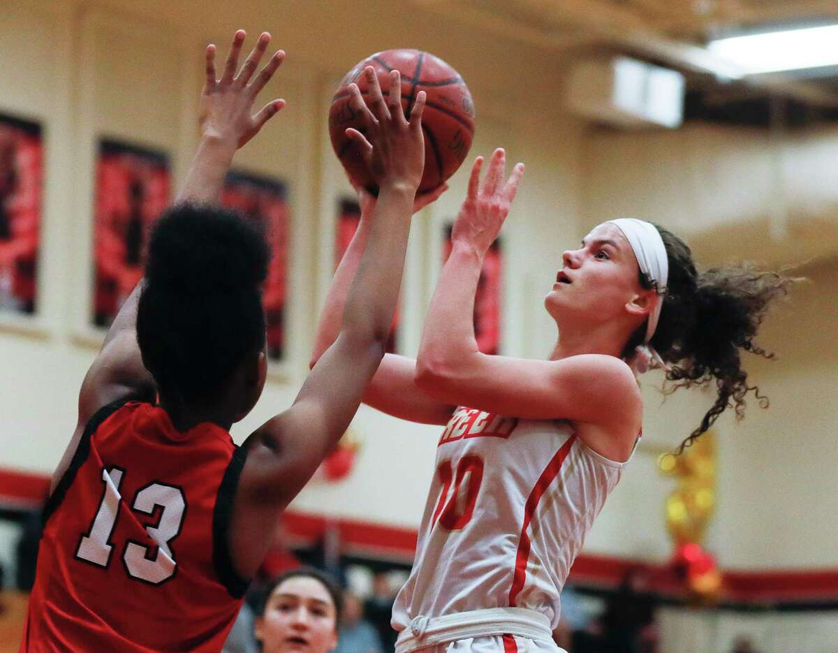 Caney Creek's Hannah Foster (10) draws a foul from Cleveland's Ki'mora Taylor (13) during the first quarter of a District 20-5A high school basketball game at Caney Creek High School, Wednesday, Jan. 27, 2021, in Grangerland.