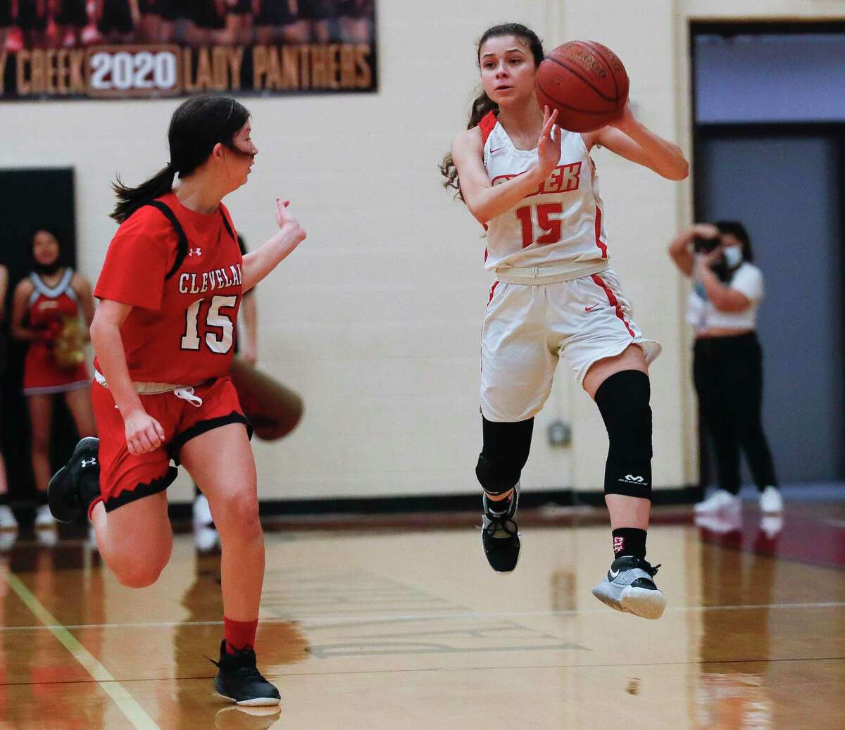Caney Creek's Brooklynn Beaza (15) makes a pass down court as Cleveland's Angeline Garland (15) defends during the first quarter of a District 20-5A high school basketball game at Caney Creek High School, Wednesday, Jan. 27, 2021, in Grangerland.