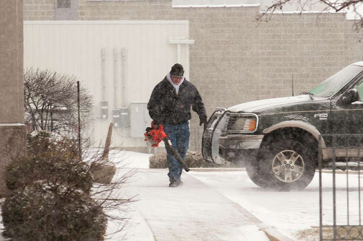 Curt Castleberry, who handles maintenance for The Farmers State Bank at Trust Co. in downtown Jacksonville, uses a leaf blower Wednesday to remove snow from the sidewalk outside the bank. The National Weather Service was predicting that west-central Illinois would receive from 1 to 3 inches of snow.