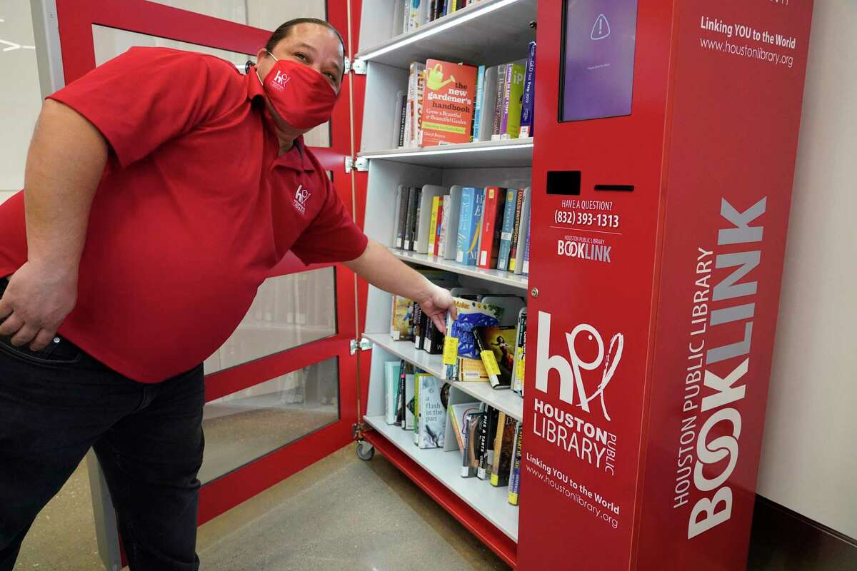 John Plail, a library services specialist, demonstrates the Booklink self-service kiosk at the Dixon TECHLink Library Powered by Aramco, 8002 Hirsch Road, Wednesday, Jan. 27, 2021 in Houston. The new library was rebuilt in the same location as the Amanda Dixon Neighborhood Library which was damaged beyond repair after Hurricane Harvey. It bridges the technology divide with the latest interactive technology to enhance learning with free access to computers and state-of-the-art technologies.