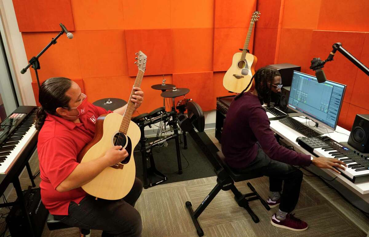 John Plail, a library services specialist, left, and Kenneth Thomas a senior customer clerk, right, demonstrate the music studio at the Dixon TECHLink Library Powered by Aramco, 8002 Hirsch Road, Wednesday, Jan. 27, 2021 in Houston. The new library was rebuilt in the same location as the Amanda Dixon Neighborhood Library which was damaged beyond repair after Hurricane Harvey. It bridges the technology divide with the latest interactive technology to enhance learning with free access to computers and state-of-the-art technologies.
