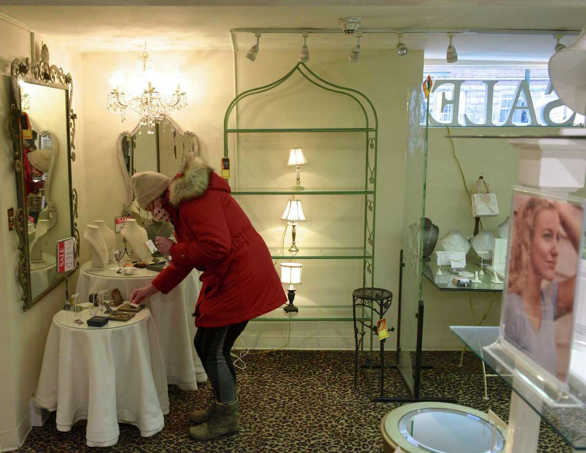 """Ilze Giambrone, of Ridgefield, shops in the Turkey Ridge gift shop. Nadine Dolhy owner of the shop is closing the doors after almost 22 years in that location. Ridgefield, Conn, Wednesday, January 27, 2021. """"I just made a quick decision,"""" Dolhy said. """"My back hurts and I need to take some rest. Retail-I've been in it my whole life and retail can be exhausting."""" """"It's a large storefront, and it's tough to be here seven days a week at my age,"""" she added. She put up a sign announcing the closure last Friday, just over a week before the last day on Sunday."""