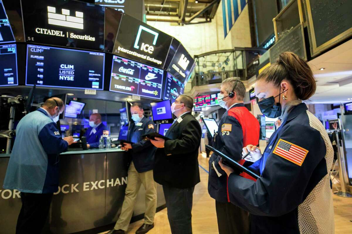 In this photo provided by the New York Stock Exchange, trader Samantha Tavares, right, works with colleagues on the floor, Wednesday, Jan. 27, 2021. In response to stock market volatility surrounding companies such as GameStop, Greenwich-based brokerage Interactive Brokers Group announced new trading restrictions affecting stocks and options of GameStop and several other companies.