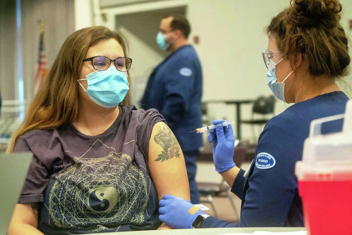Lewis and Clark Community College Health Sciences student Elizabeth Hanke receives a COVID-19 vaccine from L&C Nursing student Rachel Cauley Tuesday in The Commons during a clinic coordinated by the Madison County Health Department.