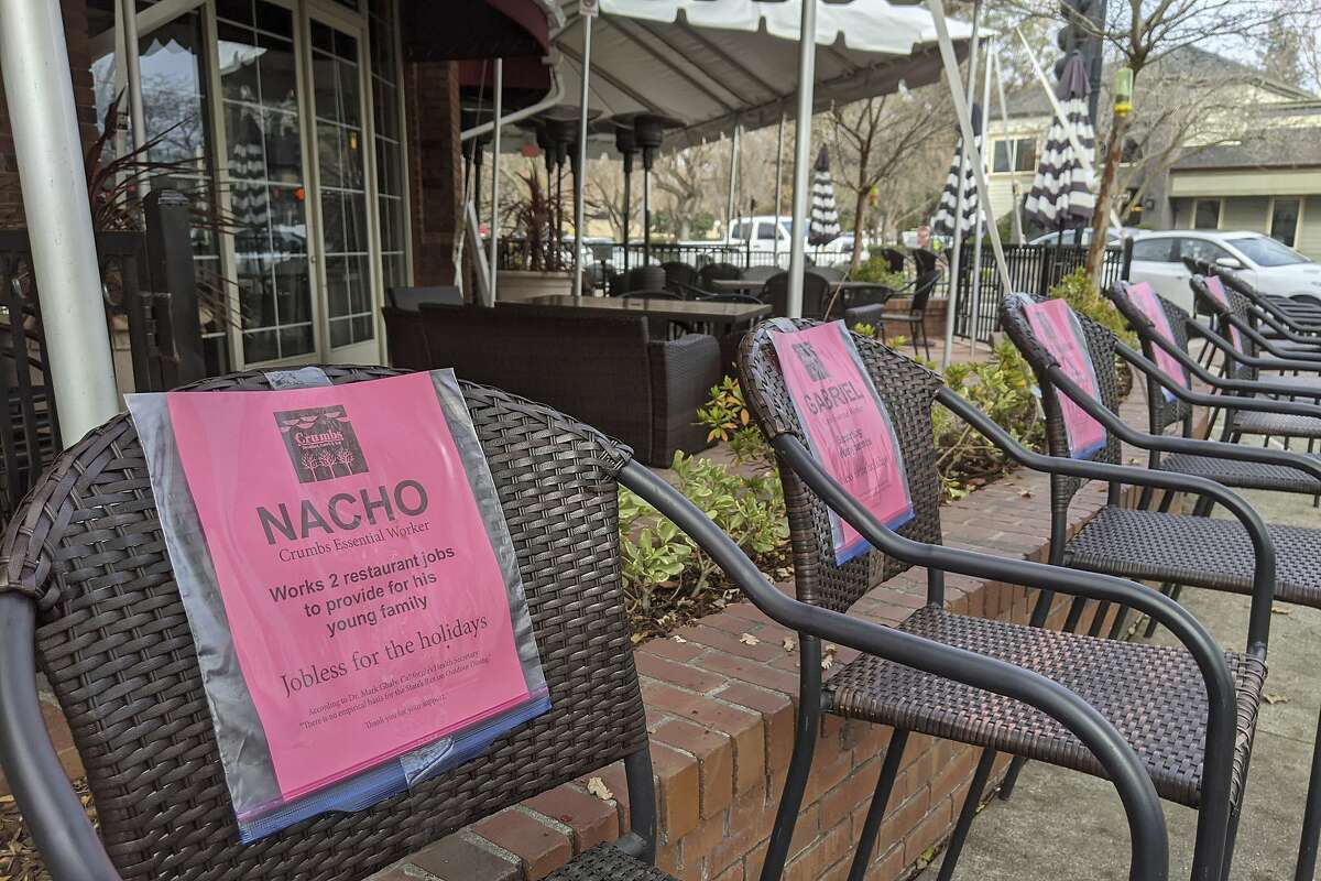 A line of empty chairs bears the names of workers who have lost their jobs during the pandemic outside the Crumbs restaurant in Danville in December. Restaurants were allowed to reopen for outdoor dining this week as the state lifted stay-at-home restrictions.
