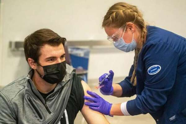 A COVID-19 vaccination is administered at Lewis and Clark Community College.