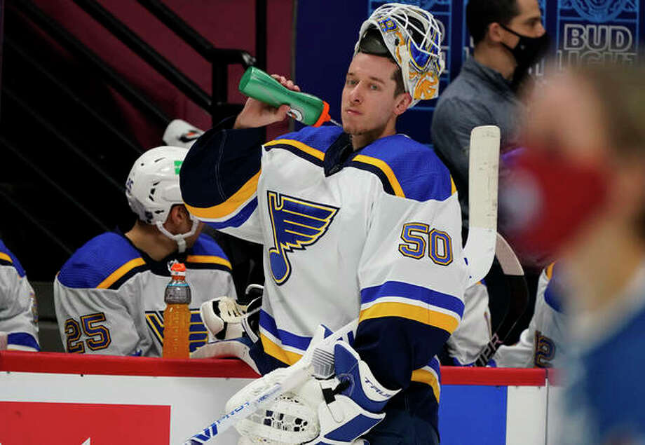 St. Louis Blues goaltender Jordan Binnington sprays water from his bottle during a timeout during a game against the Colorado Avalanche Jan. 13 in Denver.The Blues' game scheduled for Thursday in Las Vegas was postponed because of COVID-19 protocol issues on the Knights. Photo: Associated Press