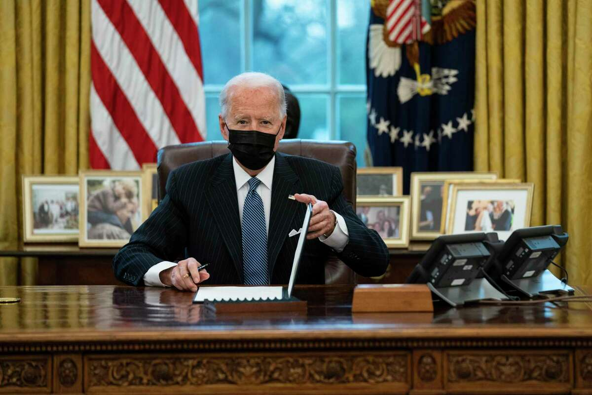 President Joe Biden looks up after singing an Executive Order reversing the Trump era ban on Transgender serving in military, in the Oval Office of the White House, Monday, Jan. 25, 2021, in Washington. (AP Photo/Evan Vucci)