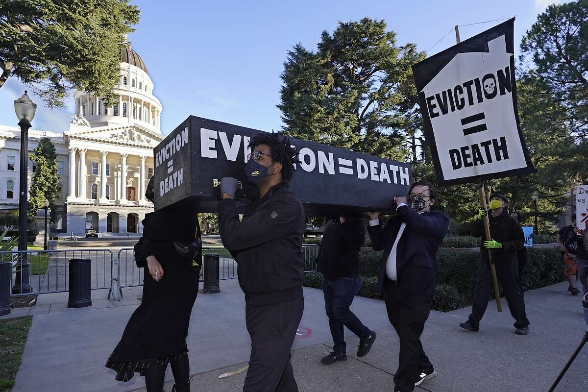 Demonstrators calling for lawmakers and Gov. Gavin Newsom to pass rent forgiveness and stronger eviction protections legislation carry a mock casket past the Capitol in Sacramento on Monday.