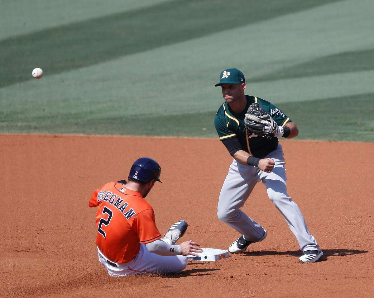 Houston Astros Alex Bregman (2) is tagged out by Oakland Athletics second baseman Tommy La Stella as Carlos Correa ground into a force out during the first inning of Game 3 of the American League Division Series, at Dodger Stadium, Wednesday, October 7, 2020, in Los Angeles.