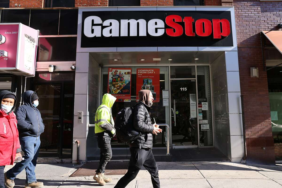 People walk by a GameStop store in Brooklyn Thursday. The troubled retailer's stock has been volatile, driven up by day traders who discuss their picks on social media.