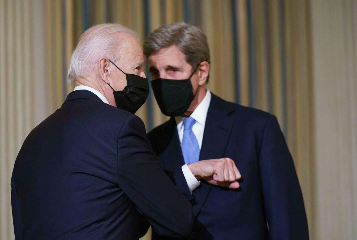President Joe Biden greets Special Presidential Envoy for Climate John Kerry as he arrives to speak on climate change before signing executive orders in the State Dining Room of the White House in Washington, DC on January 27, 2021.