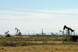 Oil rigs stand in the Loco Hills field on U.S. Highway 82 in Eddy County near Artesia, N.M., one of the most active regions of the Permian Basin. President Joe Biden is set to announce a wide-ranging moratorium on new oil and gas leasing on U.S. lands, as his administration moves quickly to reverse Trump administration policies on energy and the environment and address climate change.
