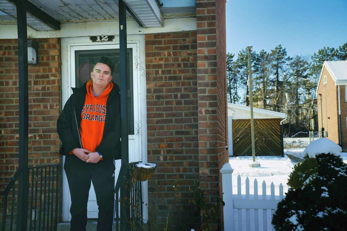Saratoga Sites resident Joe Ritchie stands on the front steps of his home on Thursday, Jan. 28, 2021, in Cohoes, N.Y. Ritchie who has raised concerns about air pollution from the neighboring Norlite aggregate plant, seen in the far background. (Paul Buckowski/Times Union)