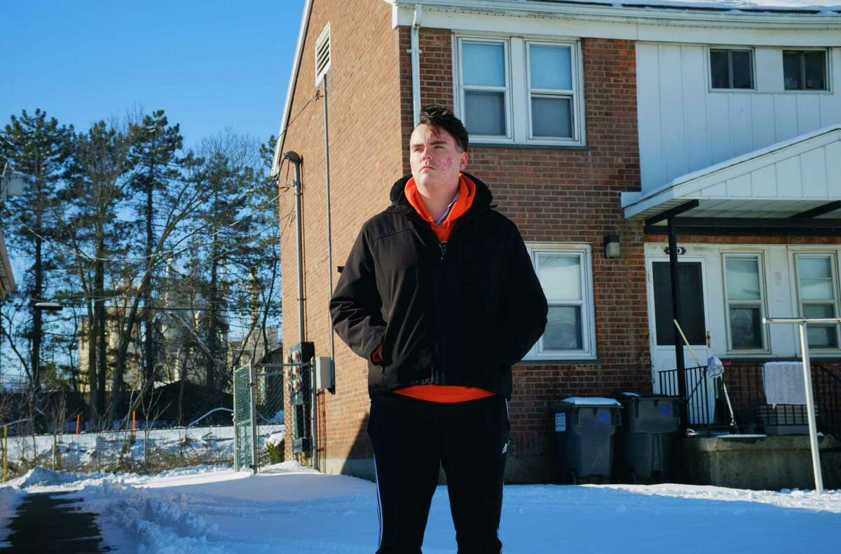 Saratoga Sites resident Joe Ritchie stands in the courtyard of the housing units on Thursday, Jan. 28, 2021, in Cohoes, N.Y. Ritchie who has raised concerns about air pollution from the neighboring Norlite aggregate plant, seen in the background. (Paul Buckowski/Times Union)