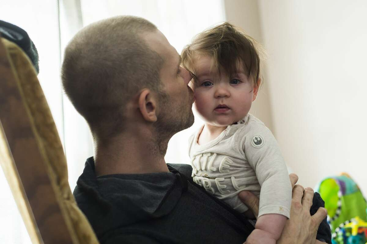 Rob Maxwell kisses his daughter, Kaelyn, 6 months, Thursday, Jan. 28, 2021 at their home in Midland. Rob was recently diagnosed with a rare type of cancer called choriocarcinoma. (Katy Kildee/kkildee@mdn.net)