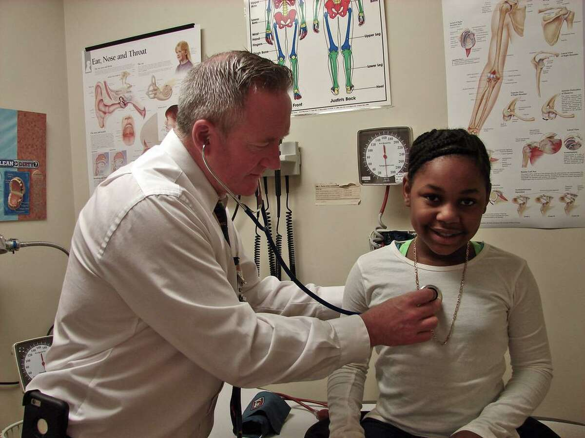 Nurse practitioner Shannon Knaggs examines a student at the health center at Augusta Lewis Troup School in New Haven.