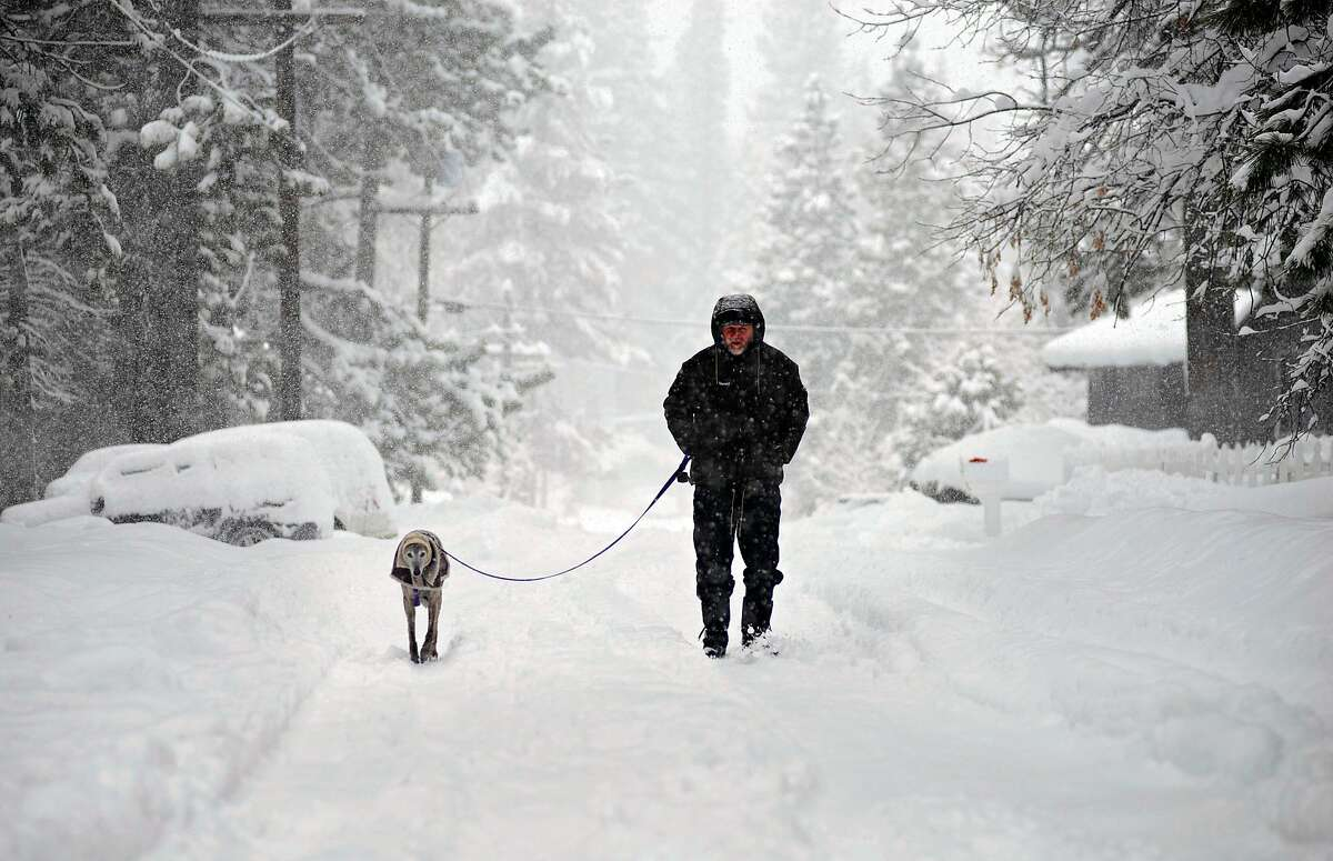 Zoltan Fenyvesi walks his dog around the neighborhood in South Lake Tahoe during a winter storm that saw snow accumulate over a foot in under 24 hours on Thursday.