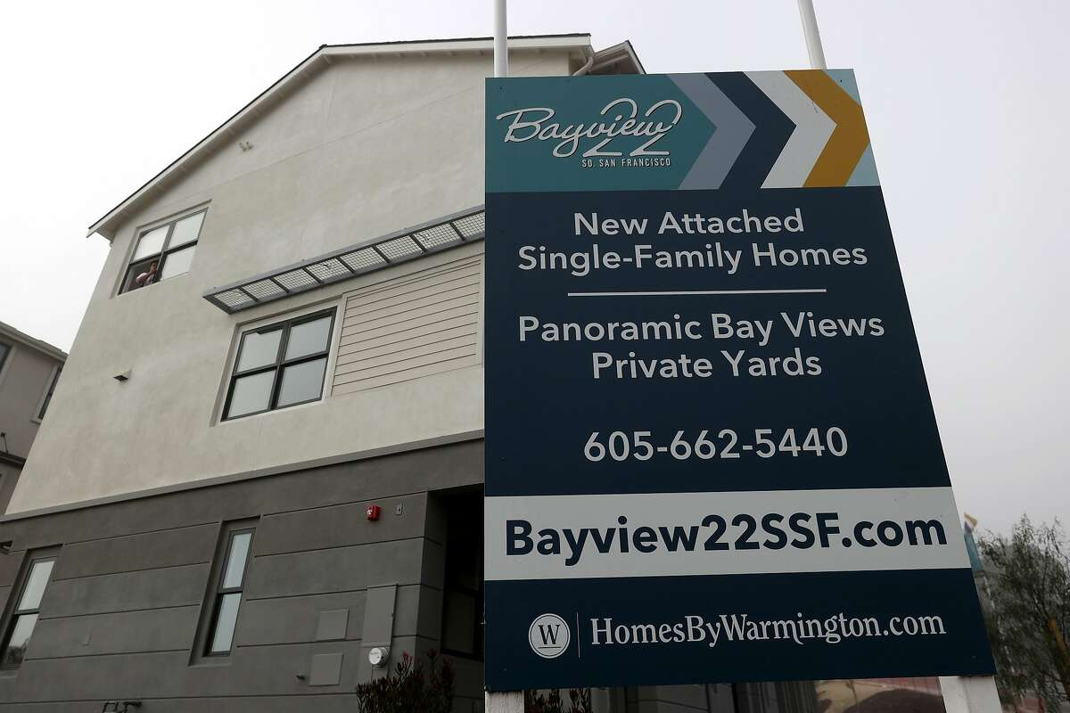 A sign is posted in front of new homes for sale in September in South San Francisco.