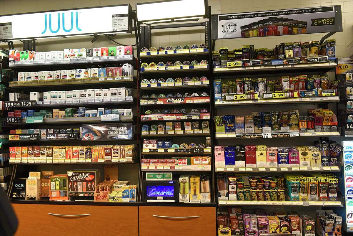 Different flavored tobacco products are seen behind the register at a convenience store.