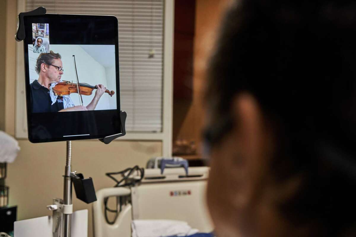 Houston Symphony first violinist Christopher Neal and the Center for Performing Arts Medicine program's Dr. Mei Rui perform for Gonzalo Alvarado in the intensive care unit at Houston Methodist Hospital.