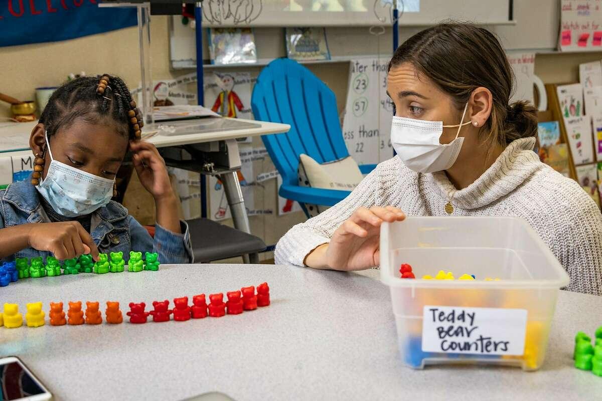 Teacher Samantha Kelly helps Raziya Wilson Brown in her first-grade class at Bayside MLK in Sausalito.