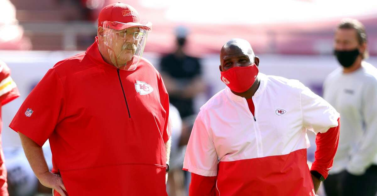 Head coach Andy Reid of the Kansas City Chiefs speaks with offensive coordinator Eric Bieniemy prior to the game against the Las Vegas Raiders at Arrowhead Stadium on October 11, 2020 in Kansas City, Missouri. (Photo by Jamie Squire/Getty Images)