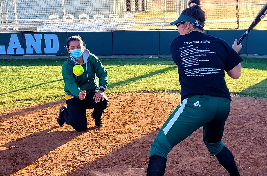 Midland College first-year softball coach Angel Castro, kneeling, is seen working with hitters during a recent practice at the Midland College softball field. Photo: Forrest Allen | Midland College