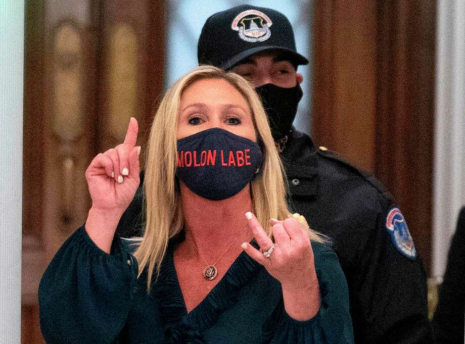 """(FILES) In this file photo taken on January 12, 2021 Representative Marjorie Taylor Greene (R-GA) shouts at journalists as she goes through security outside the House Chamber at Capitol Hill in Washington, DC. - A newly elected Republican congresswoman known for promoting QAnon conspiracy theories accused Twitter of censorship on January 17, 2021 after her account was temporarily suspended for """"multiple violations"""". Marjorie Taylor Greene was hit with the 12-hour suspension after she tweeted claims of alleged election fraud in Georgia, her home state. (Photo by ANDREW CABALLERO-REYNOLDS / AFP) (Photo by ANDREW CABALLERO-REYNOLDS/AFP via Getty Images) Photo: ANDREW CABALLERO-REYNOLDS, Contributor / AFP Via Getty Images / AFP or licensors"""