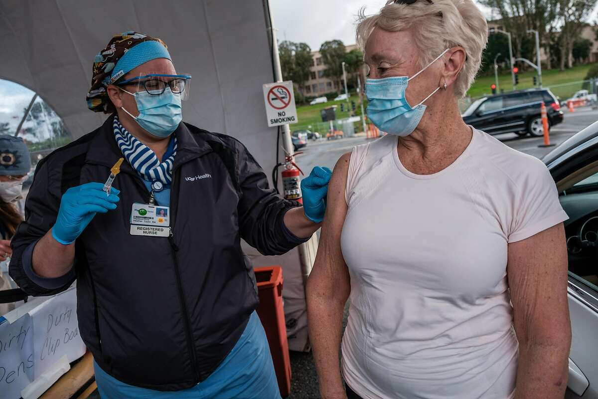 Leslie Baker receives a shot at a new mass COVID-19 vaccination center at City College San Francisco.