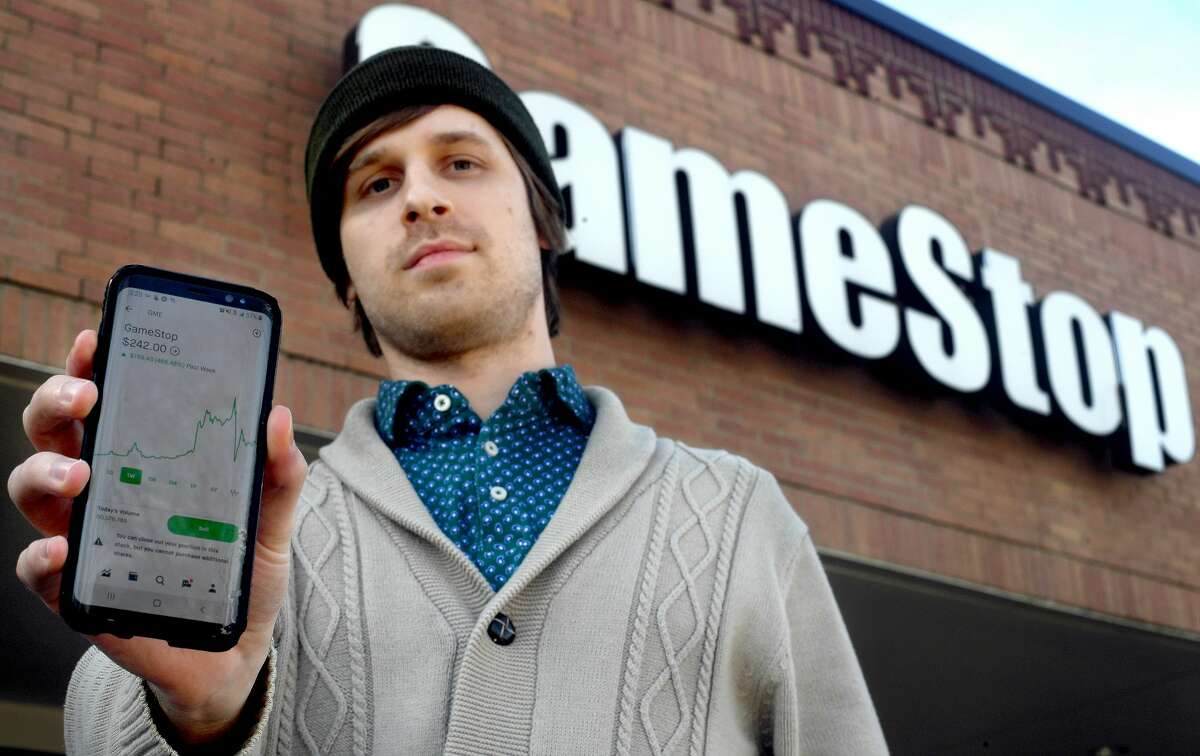 Lamar University student Caleb Peterson has watched Game Stop stock numbers flip between red and green on his phone investment app throughout the day. Peterson is among thousands of investors who saw a spike in profit as shares skyrocketed in recent days. That trajectory came to a halt Thursday morning when the stock was frozen on multiple platforms. Photo taken Thursday, January 28, 2021 Kim Brent/The Enterprise