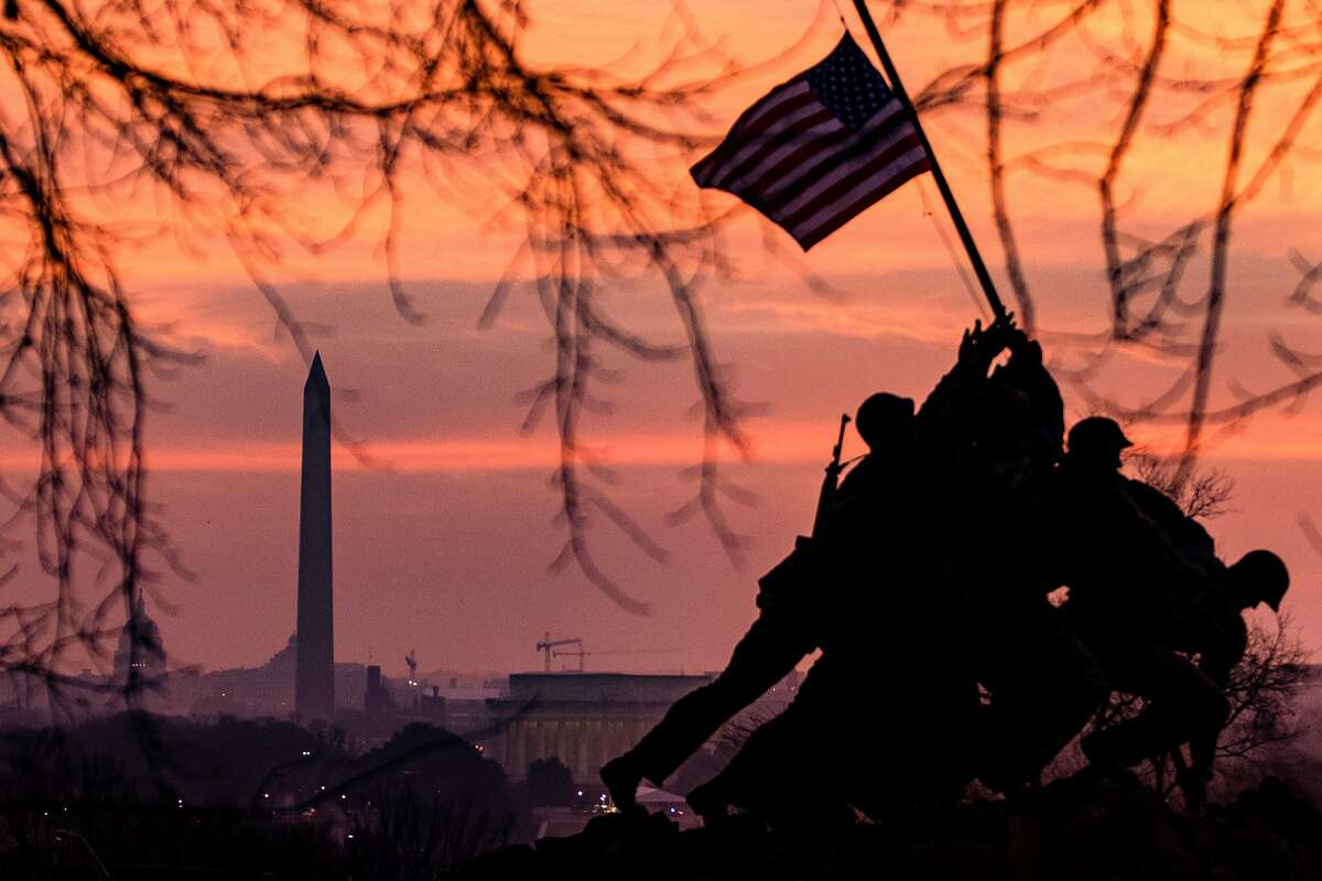 The American flag flies above the US Marine Corps War Memorial, also known as the Iwo Jima Memorial, with the Washington Monument in the distance on Jan. 15 in Arlington, Va.