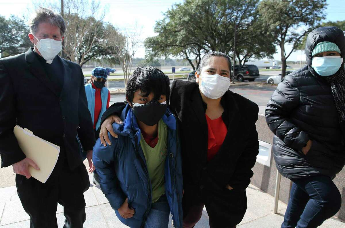 Refugee Ivan Ramirez (center) is supported by activists Pastor Jim Rigby of Austin's St. Andrew's Presbyterian Church and Carmen Zuvieta (second from right) as they approach Immigration and Customs Enforcement offices.