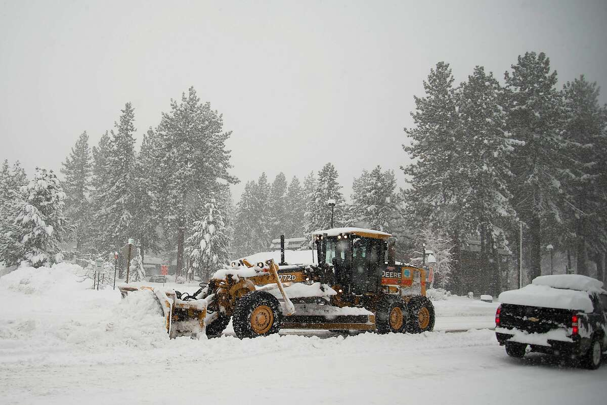 Plows work to clear lanes and medians of Highway 50 in South Lake Tahoe after a massive winter storm hit the Sierra.