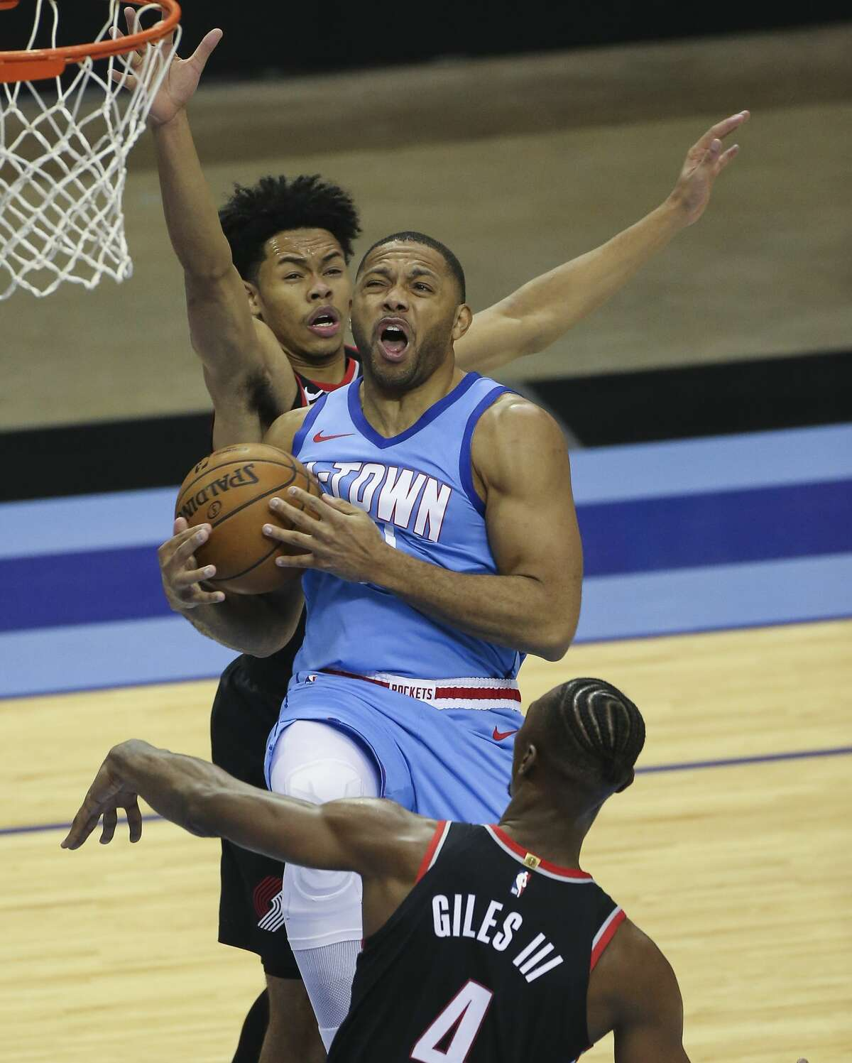 Houston Rockets guard Eric Gordon (10) cannot score a basket while Portland Trail Blazers players Anfernee Simons (1) and Harry Giles III (4) are defensingduring the fourth quarter of the NBA game Thursday, Jan. 28, 2021, at Toyota Center in Houston.