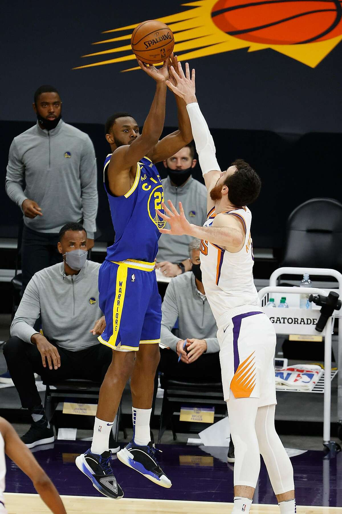PHOENIX, ARIZONA - JANUARY 28: Andrew Wiggins #22 of the Golden State Warriors puts up a three-point shot over Frank Kaminsky #8 of the Phoenix Suns during the first half of the NBA game at Phoenix Suns Arena on January 28, 2021 in Phoenix, Arizona. NOTE TO USER: User expressly acknowledges and agrees that, by downloading and or using this photograph, User is consenting to the terms and conditions of the Getty Images License Agreement. (Photo by Christian Petersen/Getty Images)