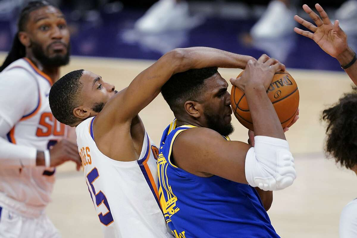 Phoenix forward Mikal Bridges (left) fouls Golden State's Kevon Looney in the first half. Looney started and played 16 minutes. Rookie center James Wiseman came off the bench to score five points and grab a team-leading six rebounds in 19 minutes.